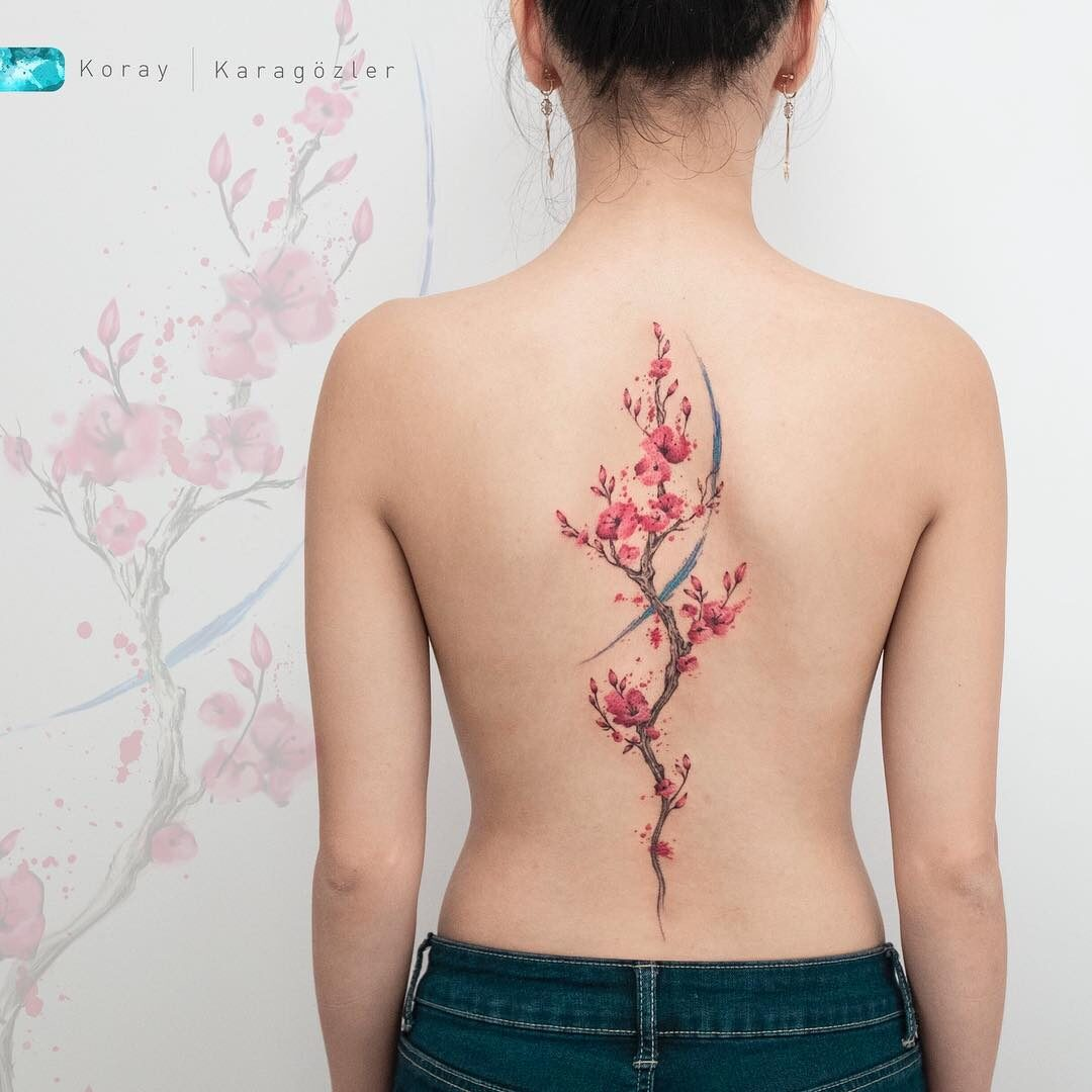 Tatuaż przedstawiający kwiat wiśni na plecach kobiety.