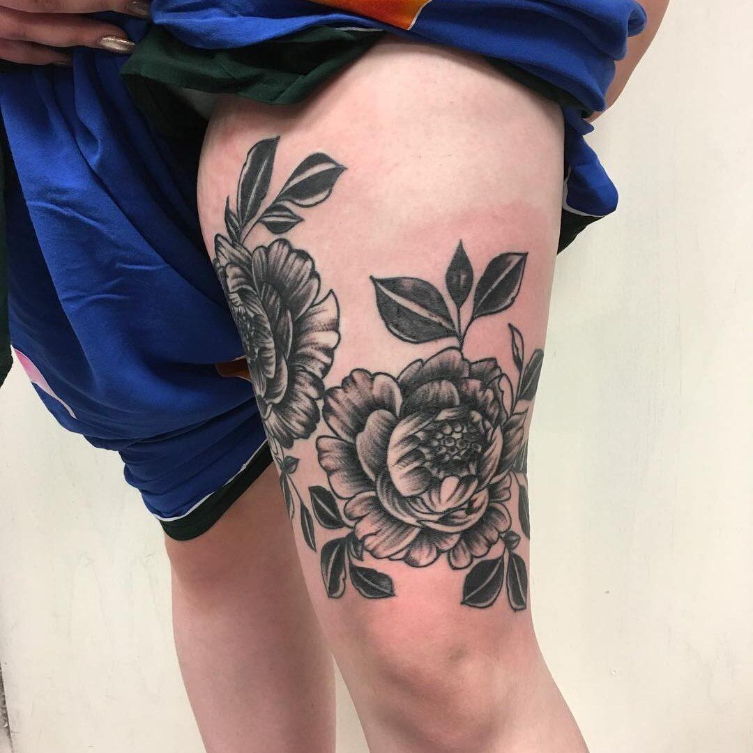 Tatuaż czarnej róży na udzie