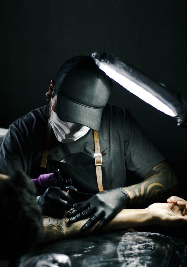 Tatuażysta wykonujący tatuaż