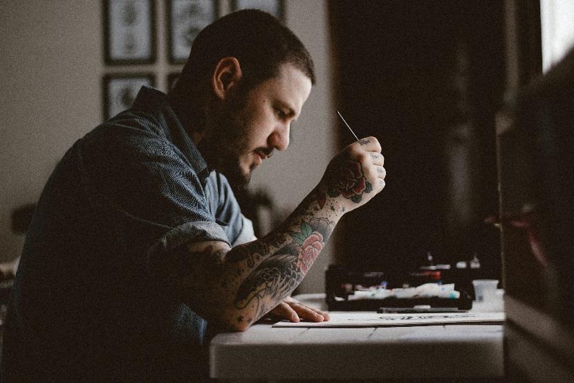 Mężczyzna wykonujący projekt tatuażu.
