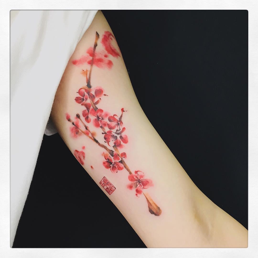 Tatuaż przedstawiający kwiat wiśni na rece