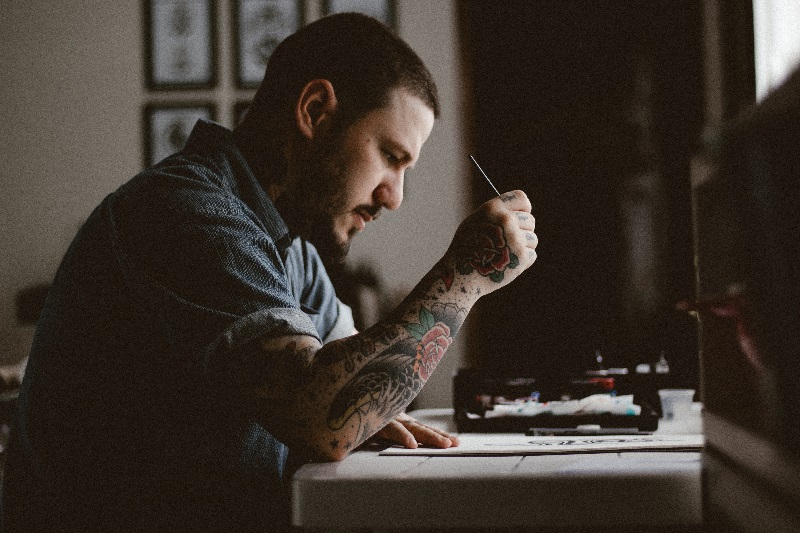 Tatuator projektujący wzór tatuażu na kartce papieru