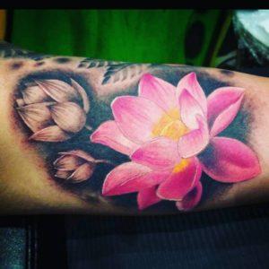 Tatuaż przedstawiający różowy kwiat lotosu.