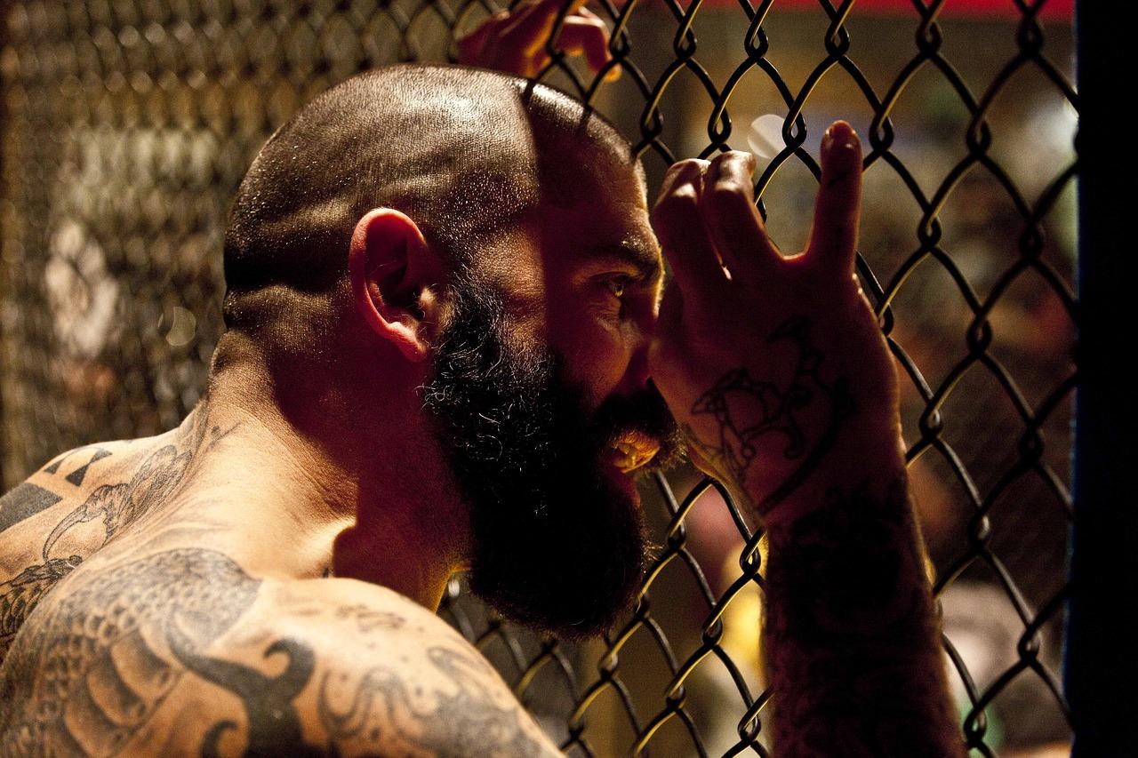Mężczyzna z tatuażami na plecach za kratami celi więziennej.