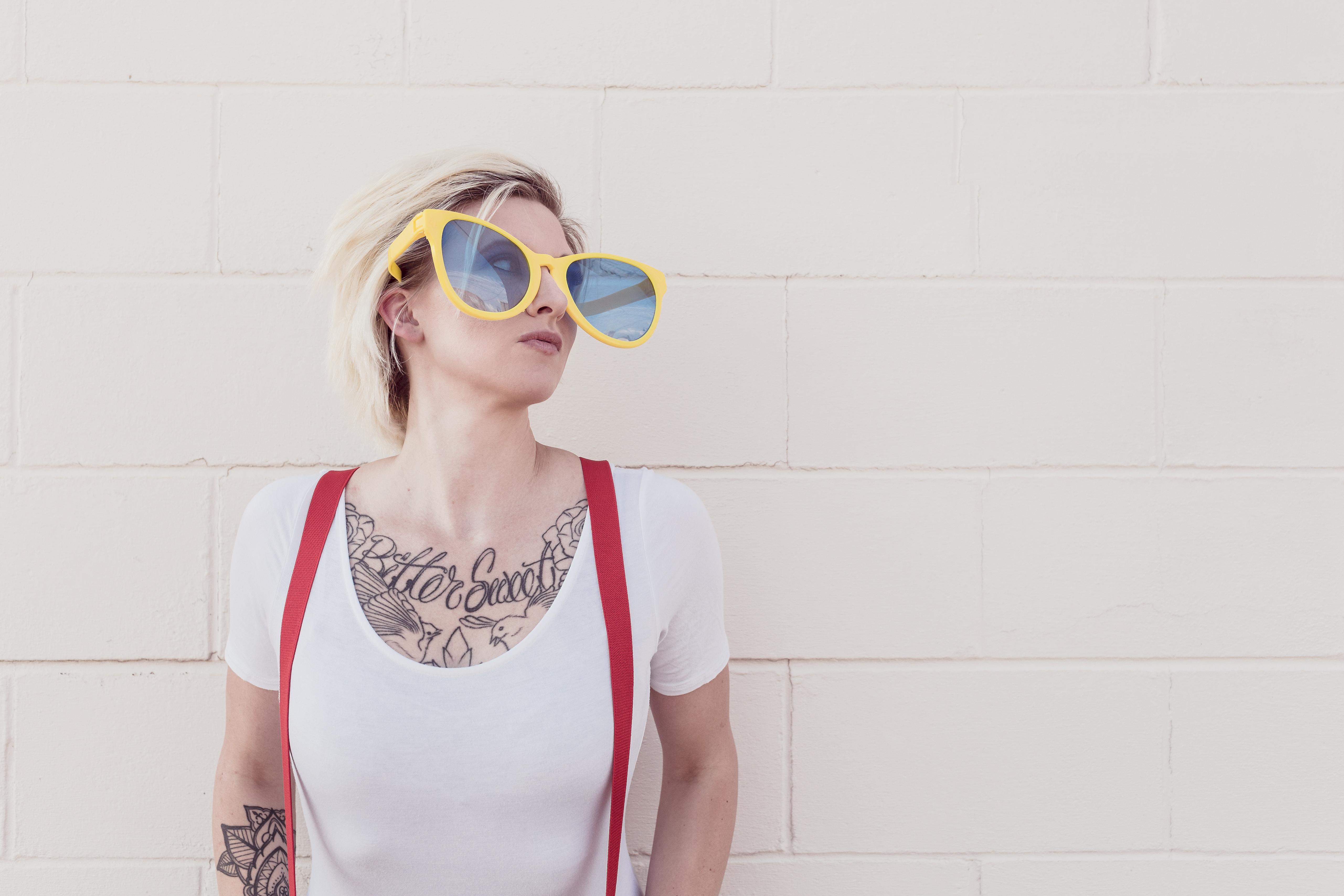 Kobieta z tatuażem i okularami przeciwsłonecznymi.